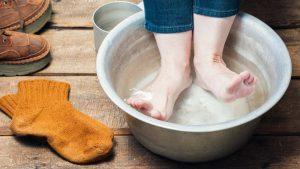 Füße in einer Schale mit Wasser