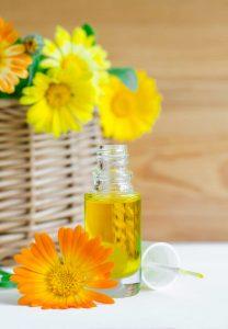 Kleine Flasche mit Ringelblumenöl und Ringelblumen Blüten daneben
