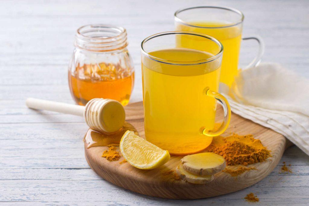 Teeglas mit Ingwer, Zitrone und Kurkuma auf Holzbrett