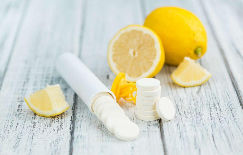 Vitamin C Tabletten und Zitronen auf Holztisch