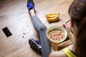 Mädchen isst Haferflocken mit Beeren nach dem Training