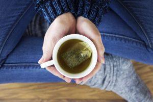 Frau hält eine Tasse Tee in der Hand