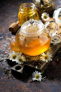 Frischer Kamillentee mit Blüten in einer Glaskanne