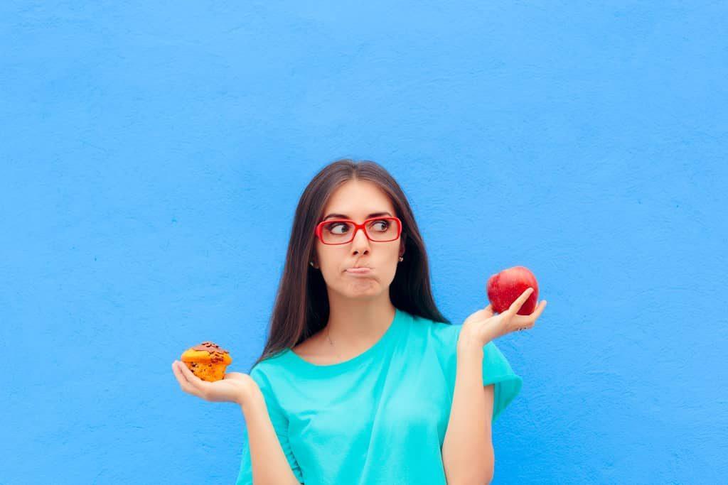 Eine Frau hält einen Apfel und einen Muffin in der Hand
