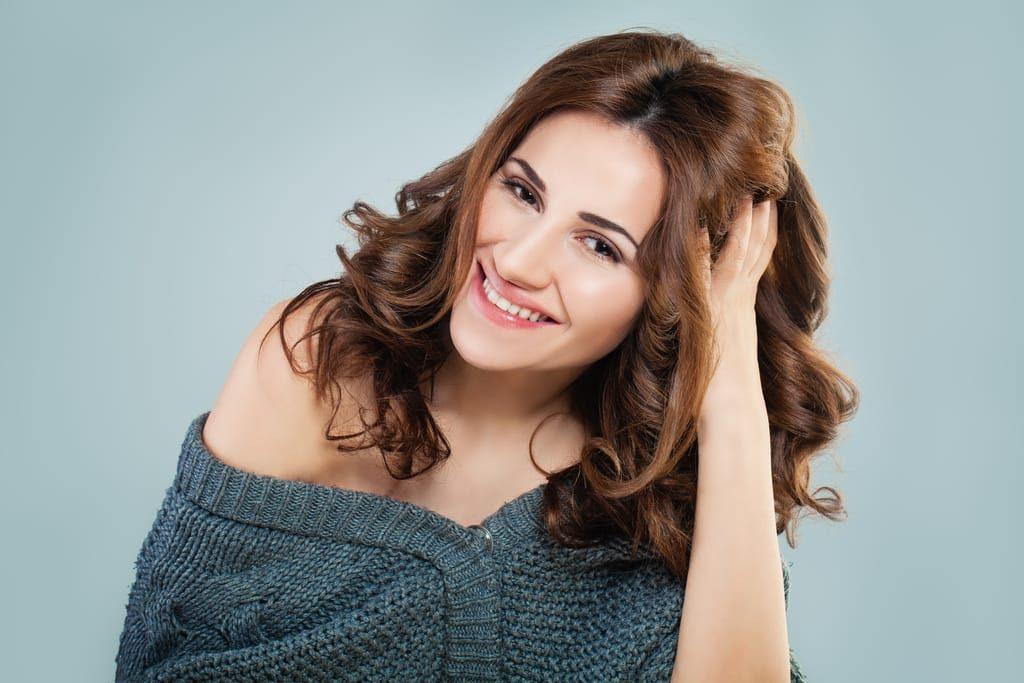 Frau greift sich in ihr gepflegtes Haar.